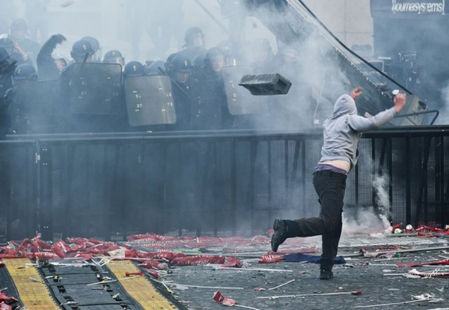 A fan throws debris at riot police in the clash between rioters and police forces during the PSG title celebration-football