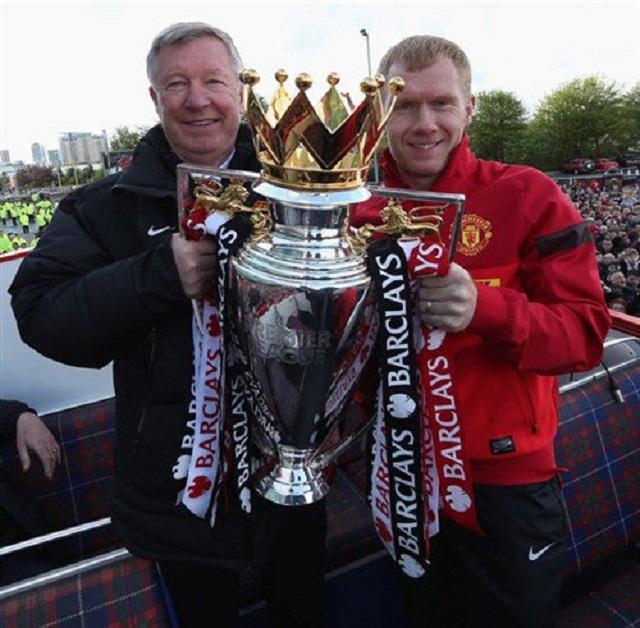 Paul Scholes and Sir Alex Ferguson exhibiting the English Premier League trophy 2013