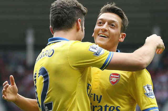 Ozil celebrates with Giroud with the assist he gives