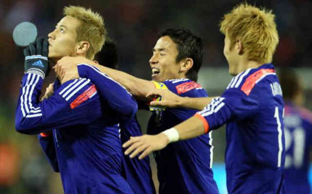 Honda celebrates his goal with team mates